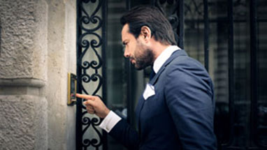 Man in a suit ringing a doorbell to advise the owner that he is about to repossess his car.